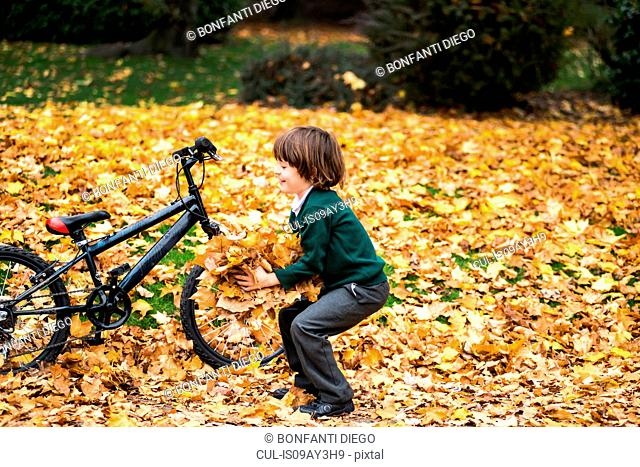 Boy in park with bike playing in autumn leaves
