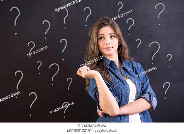 Young woman with doubtful expression and question marks on the blackboard behind her
