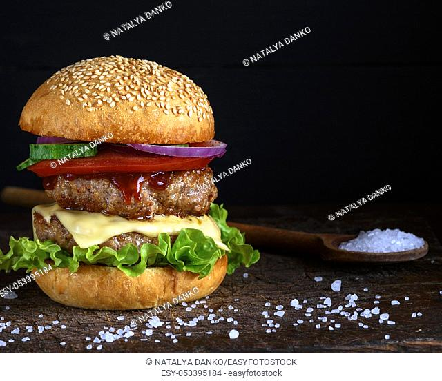 cheeseburger in a bun with sesame seeds, in the middle fresh vegetables and meat cutlets, black background