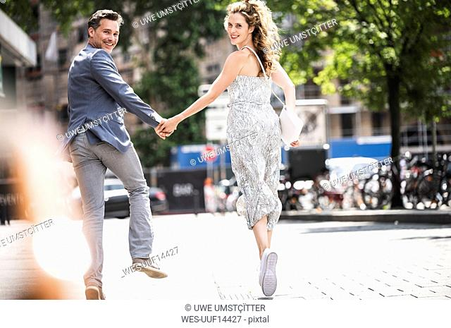 Happy carefree couple running in the city