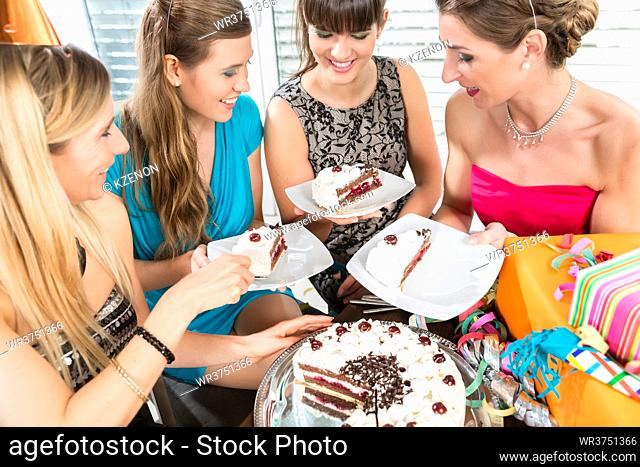Four beautiful women and best friends smiling while sharing a tasty birthday cake during surprise anniversary at home