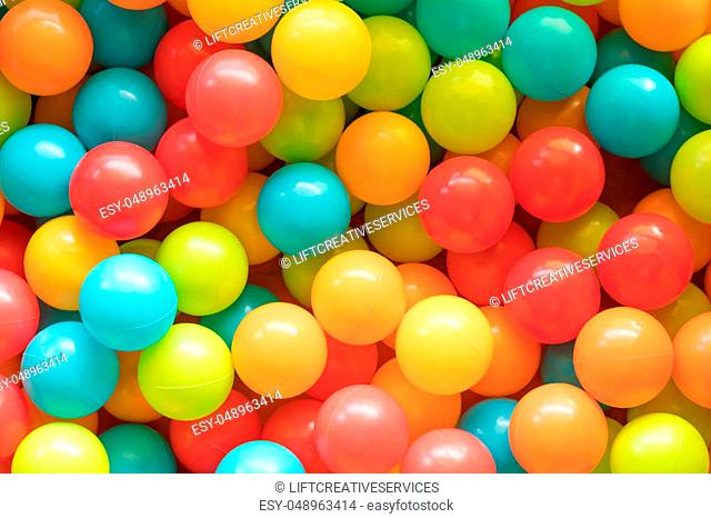 Multi colored, highly saturated plastic balls, in soft-play ball-pit, at a child's play-park