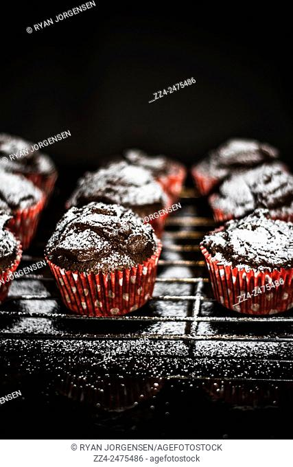 Vertical baked cupcake tray with sprinkles of sugary sweetness on black kitchen bench. Home made desserts