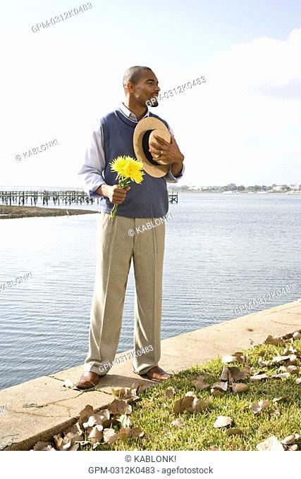 Portrait of African American gentleman standing near water at garden party