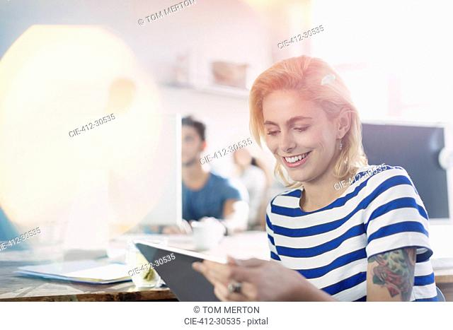 Smiling creative young businesswoman using digital tablet