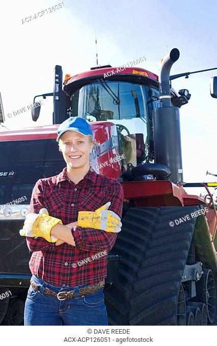 farm girl next to a Quadtrac tractor, near Dugald, Manitoba, Canada