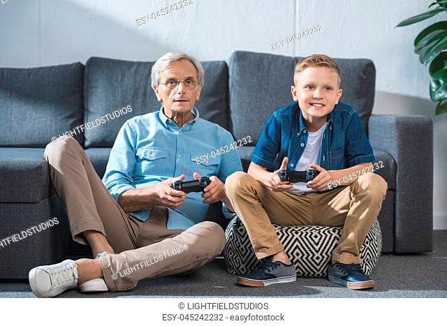 grandfather and grandson playing video game with joysticks