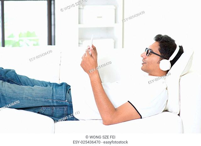 Indian guy enjoying music using digital computer tablet at home. Asian man with headset listening to song, relaxed and lying on sofa indoor