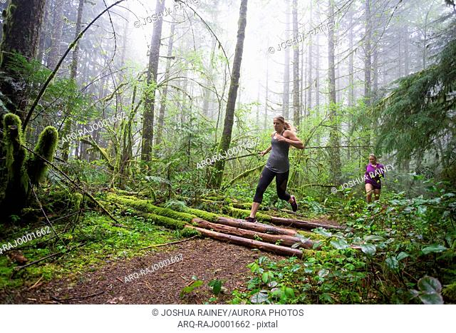 Side view of two female runners exercising in mossy forest during rain and fog, Oregon, USA