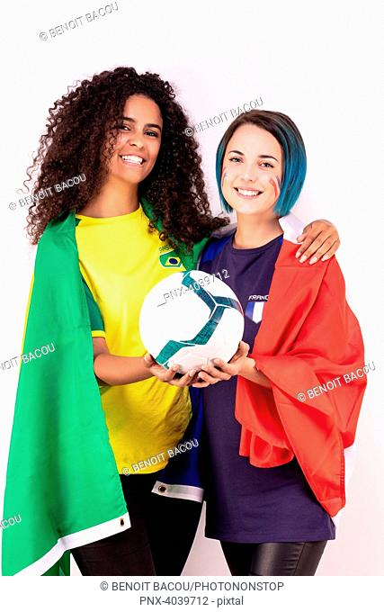 Portrait of two young fans of the Brazilian team and the French fraternising team, a ball in their hands