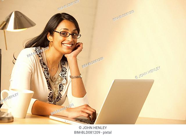 Mixed race woman typing on laptop