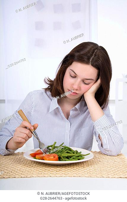 Teenage girl refusing to eat her plate of vegetables