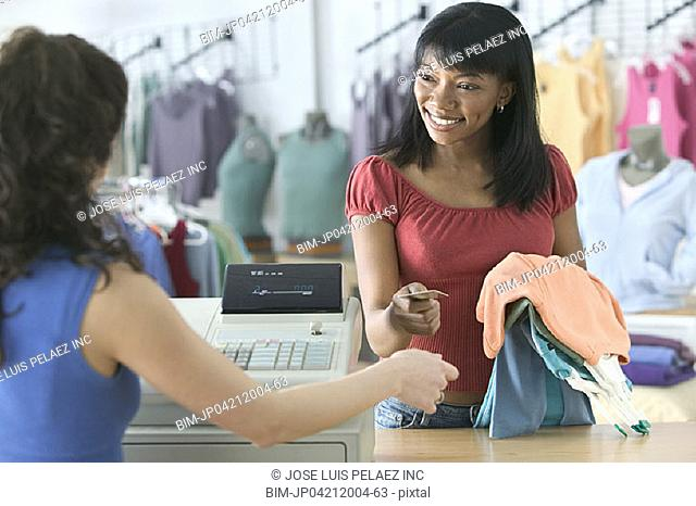 Young woman purchasing blouses