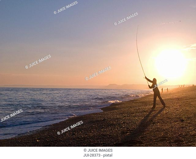 Silhouette of man casting with fishing rod into ocean at sunset