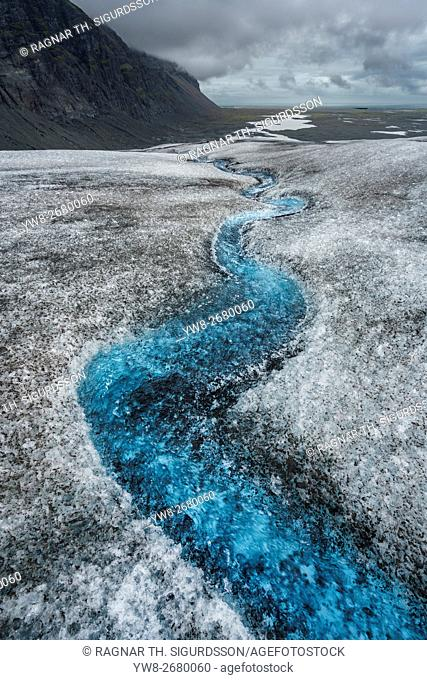 Flowing water, ice and ash on a glacier. Glacial landscape, Breidamerkurjokull, Vatnajokull Ice Cap, Eastern Iceland