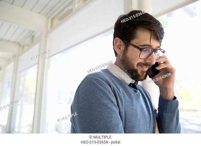 Businessman talking on cell phone looking down at window