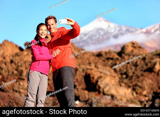 Couple taking selfie hiking in beautiful nature with smart phone. Happy couple walking enjoying view and taking pictures with smartphone