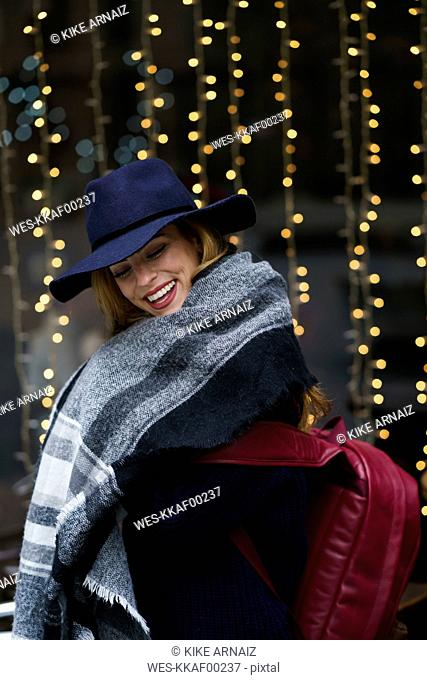 Portrait of laughing young woman wearing blue hat and scarf