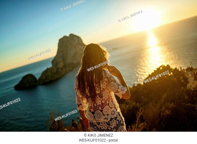 Spain, Ibiza, Woman looking at the sea and Es Vedra island at sunset