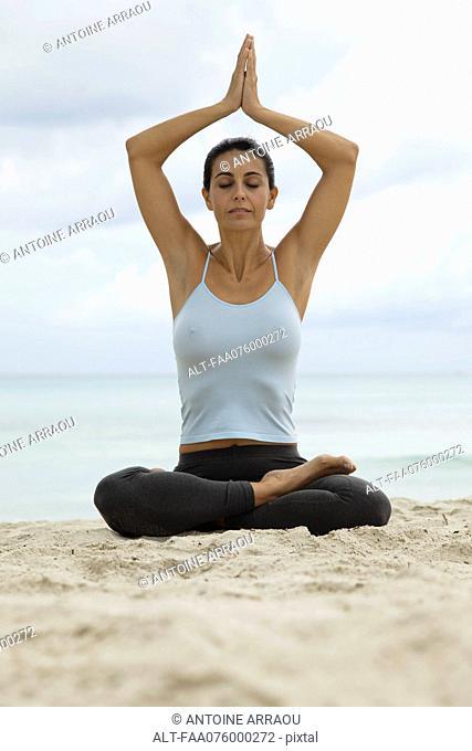 Mature woman in prayer position on beach