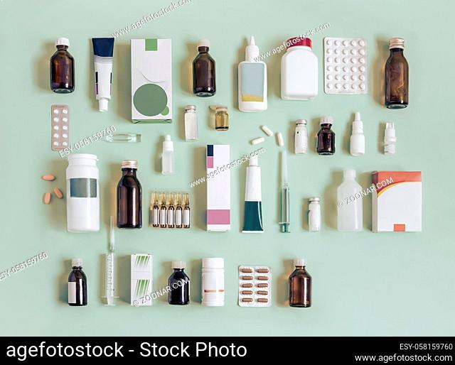 Various forms of drugs: tablets, ampoules, tinctures, blister packaging on a light green background. Place to insert text, top view