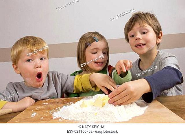 Kinder haben Spaß beim Teig kneten
