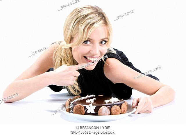 A blonde woman eating a birthday cake
