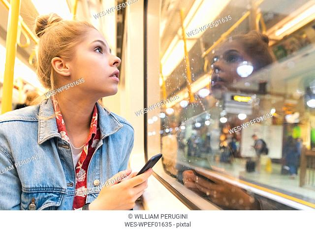 Young woman travelling by train and looking out of the window
