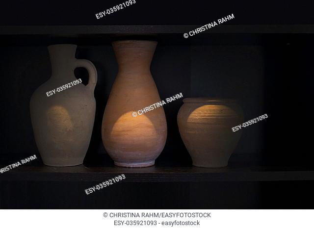 Three terracotta vases earthenware household item handmade on a dark shelf isolated on black