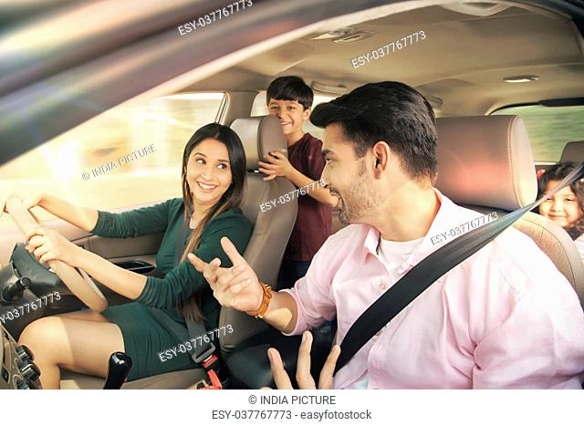 Mother driving a car during a road trip with family