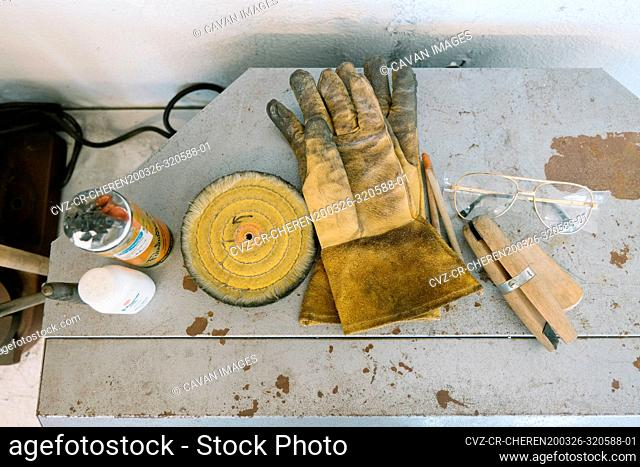 Dirty gloves rest by glasses and assorted crafting tools and resources