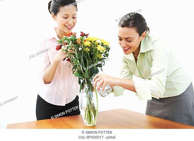 Two woman watering flowers