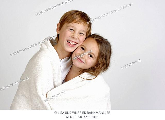 Portrait of laughing boy sharing blanket with his little sister
