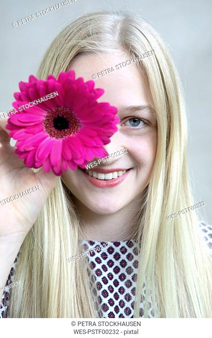Portrait of smiling blond girl with flower head of pink Gerbera