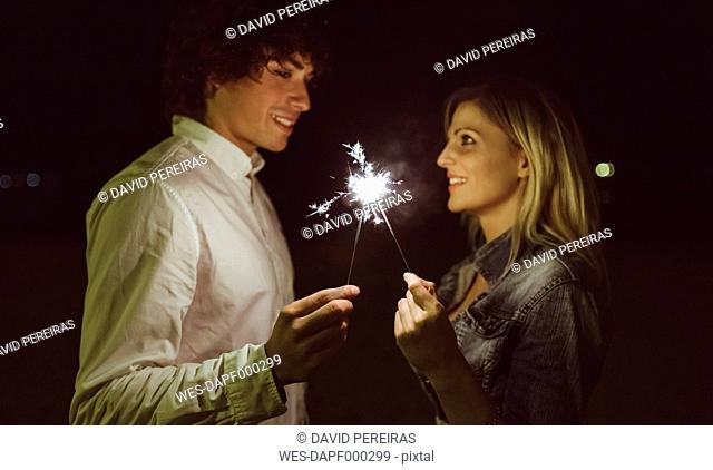 Young couple in love holding sparklers on the beach at night