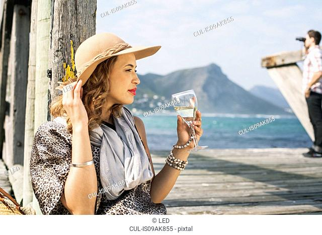 Young glamorous woman drinking wine on coastal pier, Cape Town, Western Cape, South Africa
