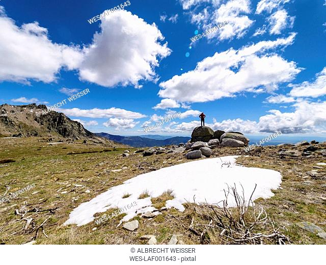 Spain, Sierra de Gredos, hiker standing on rock in mountainscape