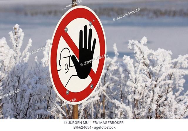 Winter landscape: stop-sign with outstretched black hand (do not enter)