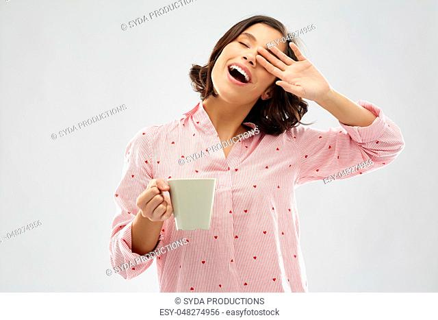 happy yawning young woman in pajama with coffee