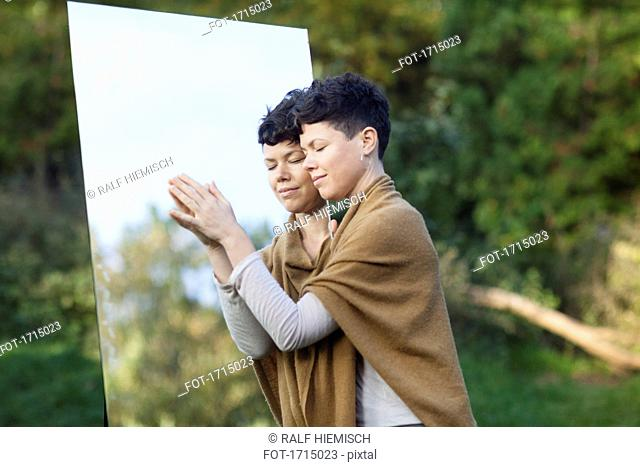 Smiling woman with closed eyes leaning on mirror while standing at park