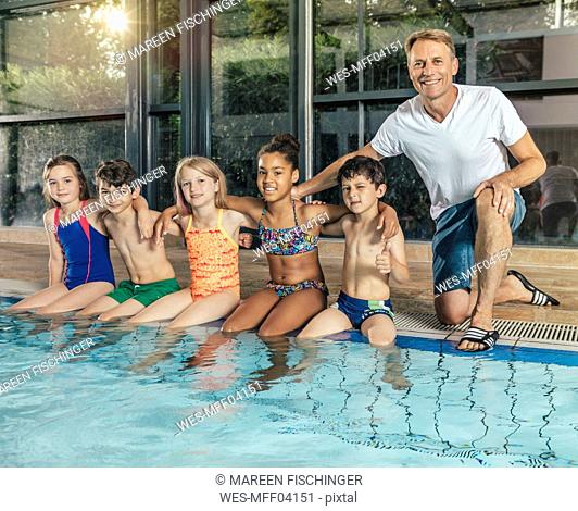 Portrait of smiling children with instructor sitting on poolside in indoor swimming pool