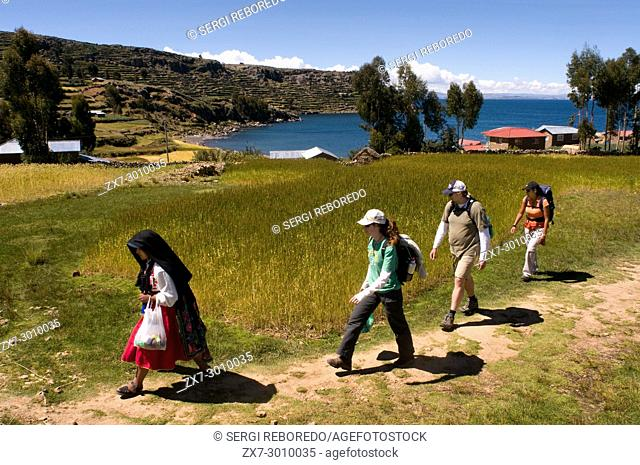 Amantani Island, Lake Titicaca, Puno, Peru. A local woman accompanies tourists to her home. When these arrive, and by means of a system of rotation