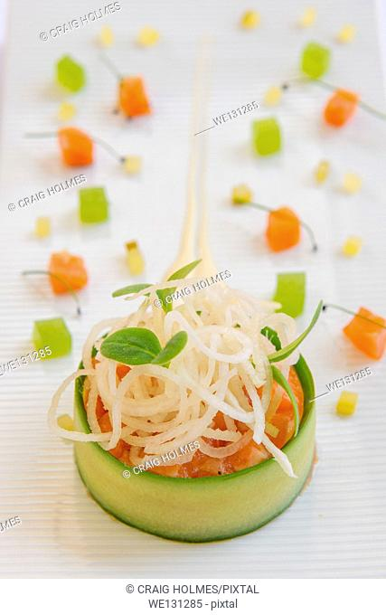 Salmon, wrapped in cucumber, topped with rice noodles