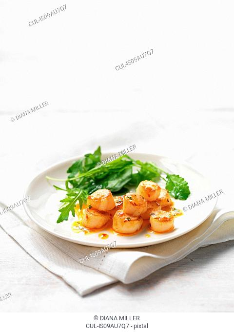 Scallops with chilli and coriander served with green salad leaves