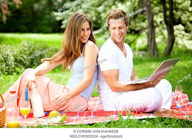 Happy couple with laptop having a picnic in park