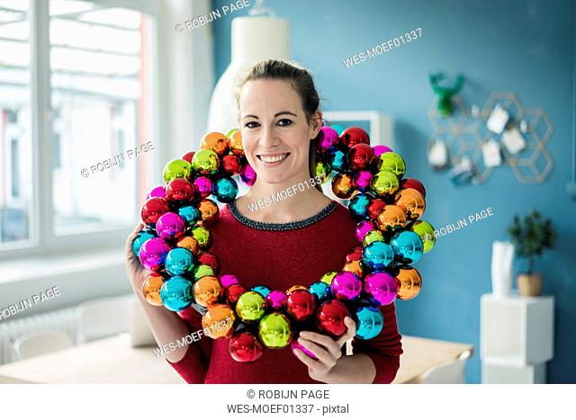 Portrait of smiling woman with colourful Christmas bauble wreath