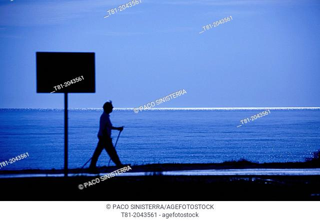 Person walking with canes in Peniscola, Castellon province, Comunidad Valenciana, Spain