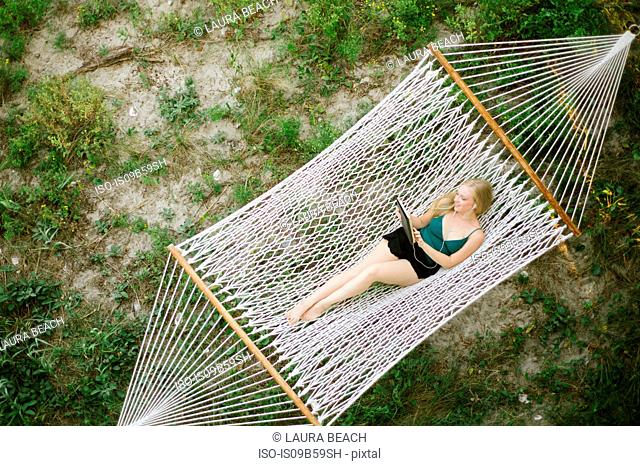Overhead view of young woman looking at digital tablet on hammock at beach