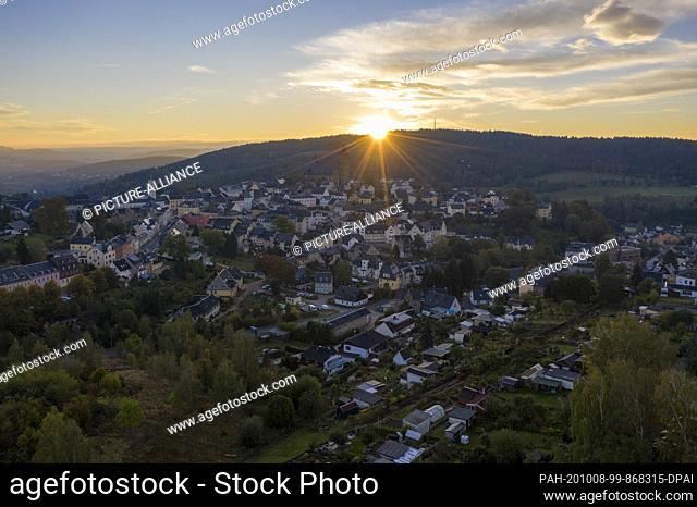 03 October 2020, Saxony, Schneeberg: The sun rises behind the Erzgebirge town of Schneeberg. The mountain town belongs to the UNESCO World Heritage region...