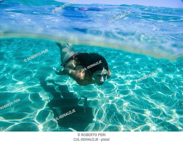 Young woman swimming underwater in ocean